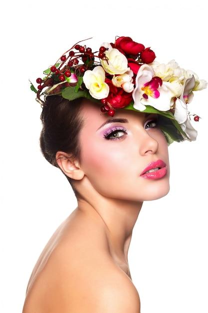 頭の上の色とりどりの花で美しいスタイリッシュな若い女性の肖像画 無料写真