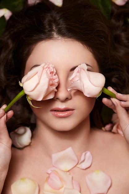 長い巻き毛と花の美しいブルネットの女性の肖像画 無料写真