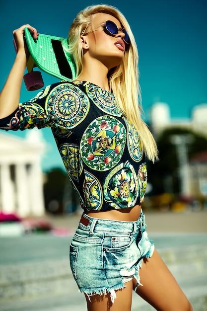 スケートボードと美しいスタイリッシュな若い女性の肖像画 無料写真
