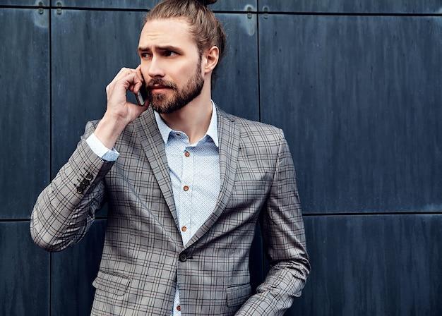 スマートフォンと言えばグレーの市松模様のスーツでハンサムな男 無料写真