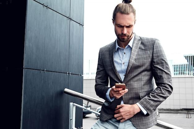 スマートフォンでグレーの市松模様のスーツでハンサムな男 無料写真