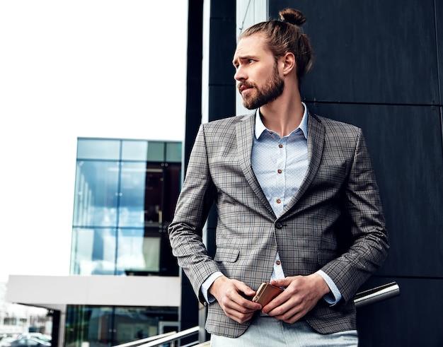 エレガントなグレーの市松模様のスーツに身を包んだセクシーなハンサムな男の肖像 無料写真