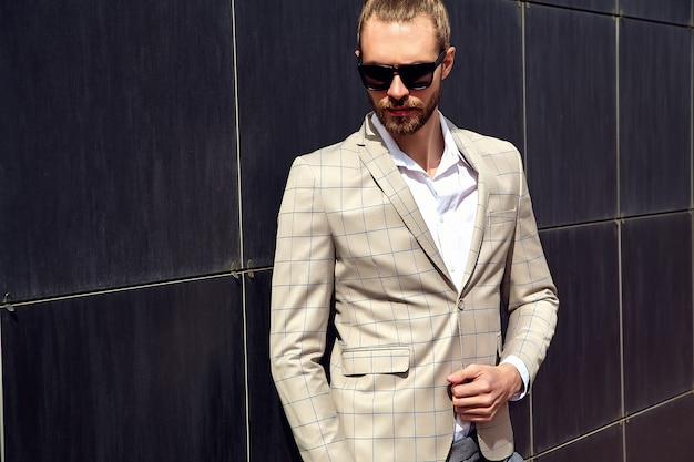 エレガントなベージュの市松模様のスーツに身を包んだセクシーなハンサムな男の肖像 無料写真