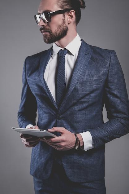 Портрет модельер красивый бизнесмен, одетый в элегантный синий костюм в очках Бесплатные Фотографии
