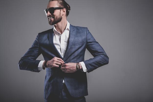灰色のポーズサングラスでエレガントな青いスーツに身を包んだハンサムなファッションスタイリッシュな流行に敏感なビジネスマンモデルの肖像画 無料写真