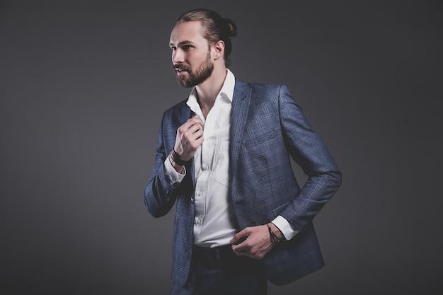 グレーでポーズエレガントな青いスーツに身を包んだハンサムなファッションスタイリッシュな流行に敏感なビジネスマンモデルの肖像画 無料写真