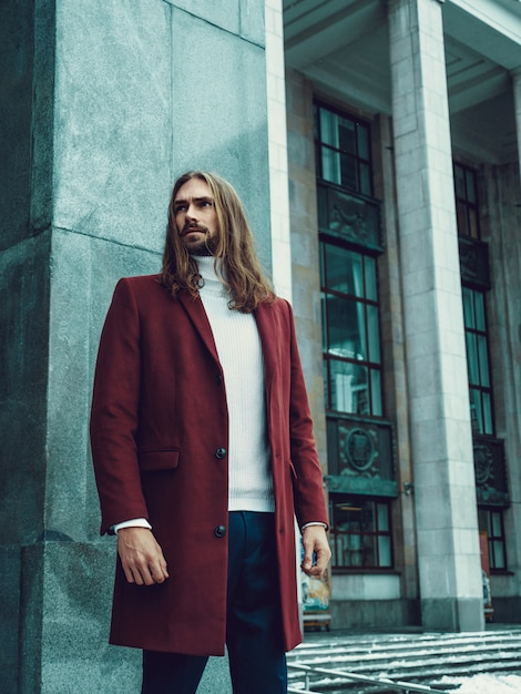 ひげが屋外でよそ見でポーズをとってハンサムな自信を持って身なりの男。赤い冬のコートと白いセーターのファッショナブルな豊富な男性モデル 無料写真