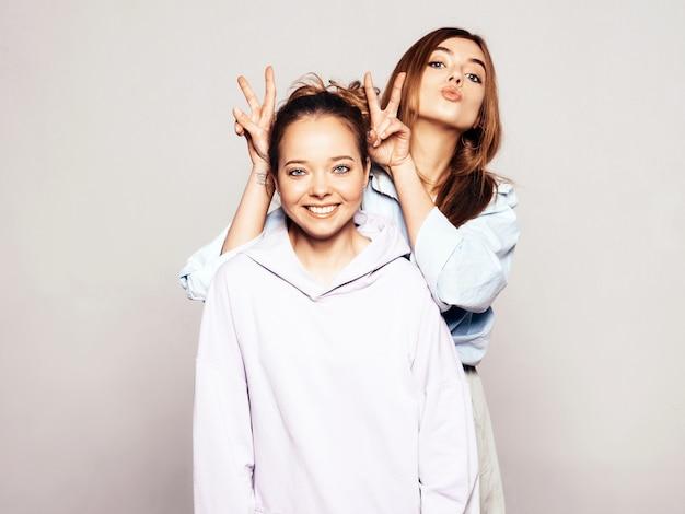 Две молодые красивые улыбающиеся девушки в модной летней одежде. сексуальные беззаботные женщины. позитивные модели Бесплатные Фотографии