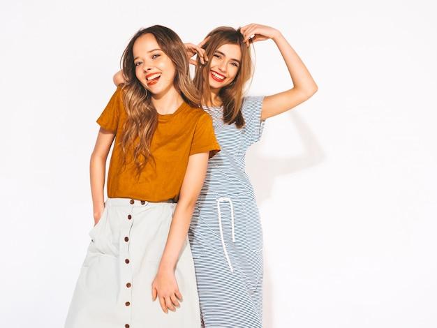Две молодые красивые улыбающиеся девушки в модной летней повседневной одежды. сексуальные беззаботные женщины. позитивные модели Бесплатные Фотографии