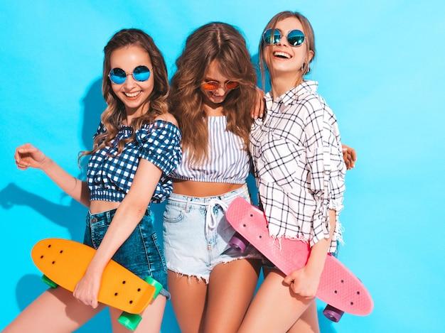 Три молодые стильные улыбающиеся красивые девушки с красочными пенни скейтборды. женщина в клетчатой рубашке летом позирует одежды. веселые позитивные модели Бесплатные Фотографии
