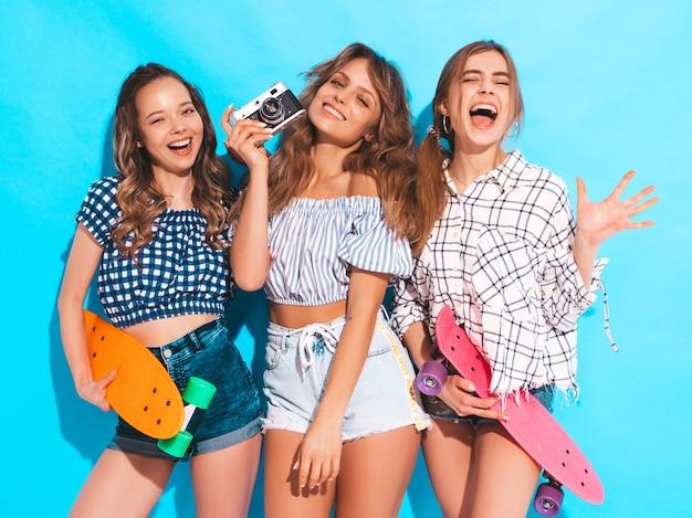 Три сексуальные красивые стильные улыбающиеся девушки с красочными пенни скейтборды. женщины в клетчатой рубашке летом позируют. модели снимают на ретро фотоаппарат Бесплатные Фотографии
