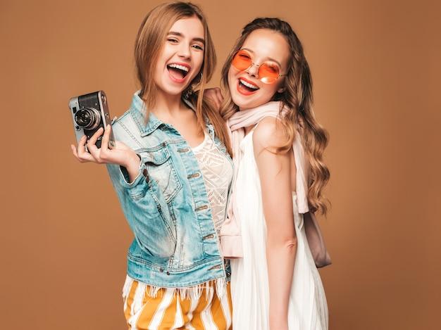 Две молодые красивые улыбающиеся девушки в модной летней повседневной одежды и солнцезащитные очки. сексуальные беззаботные женщины позируют. фотографировать на ретро камеру Бесплатные Фотографии