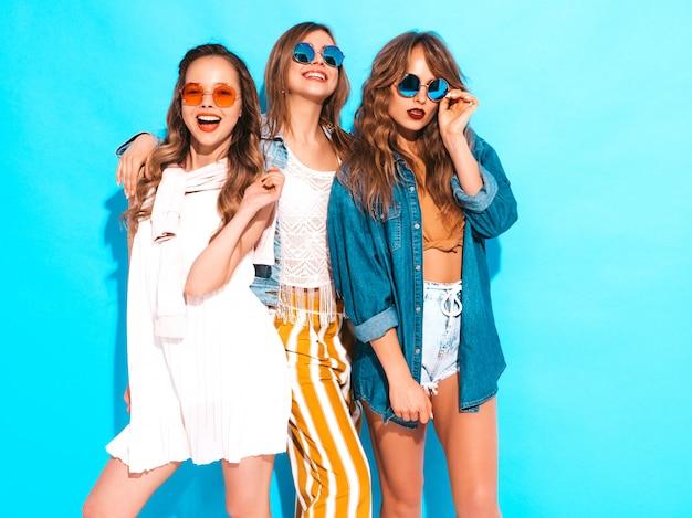 Три молодые красивые улыбающиеся девушки в модных летних повседневных платьях. сексуальные беззаботные женщины позируют. позитивные модели Бесплатные Фотографии