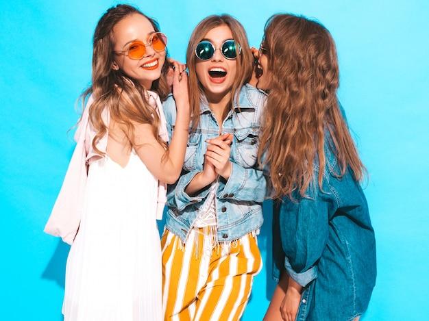 Три молодые красивые улыбающиеся девушки в модной летней повседневной одежды и круглые очки. сексуальные женщины делятся секретами, сплетнями. изолированные на синем. удивленные эмоции лица Бесплатные Фотографии