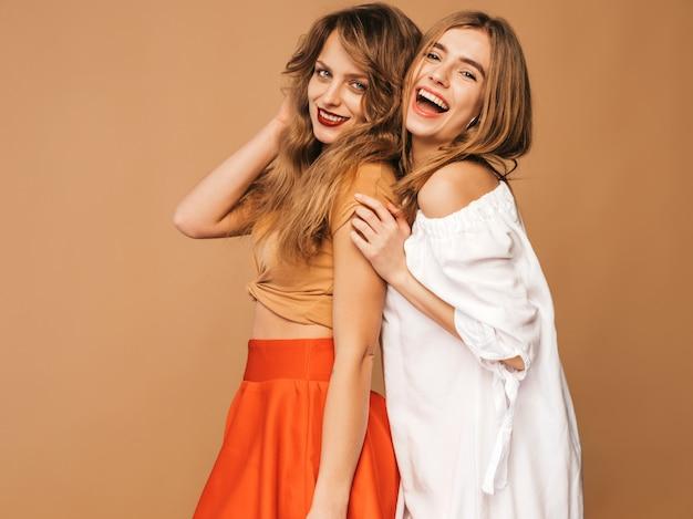 Две молодые красивые улыбающиеся девушки в модной летней одежде. сексуальные беззаботные женщины позируют. позитивные модели Бесплатные Фотографии