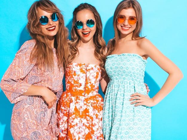 Три молодые красивые улыбающиеся девушки в модных летних повседневных платьях и в солнцезащитных очках. сексуальные беззаботные женщины позируют. Бесплатные Фотографии