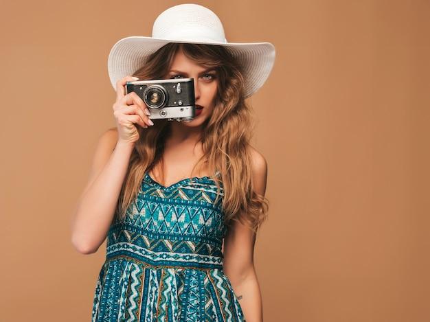 インスピレーションと写真を撮ると夏のドレスを着て陽気な笑顔の若い女性の肖像画。レトロなカメラを保持している女の子。帽子でポーズをとるモデル 無料写真