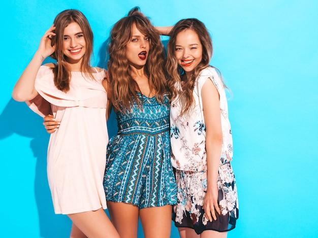 Три молодые красивые улыбающиеся девушки в модных летних повседневных платьях. сексуальные беззаботные женщины позируют. фотографировать на ретро камеру Бесплатные Фотографии