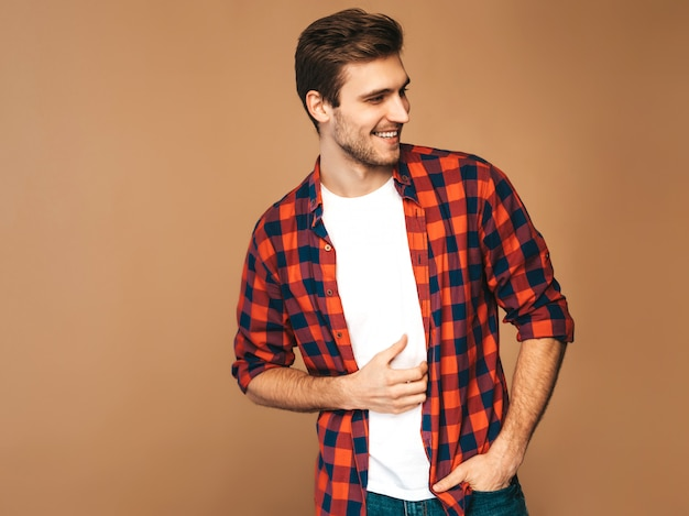 Портрет красивые улыбающиеся стильный молодой человек модель, одетый в красной клетчатой рубашке модный мужчина позирует Бесплатные Фотографии
