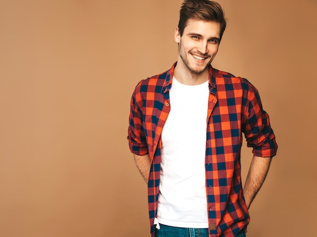 赤い格子縞のシャツに身を包んだハンサムな笑顔スタイリッシュな若い男モデルの肖像画。ファッション男のポーズ 無料写真