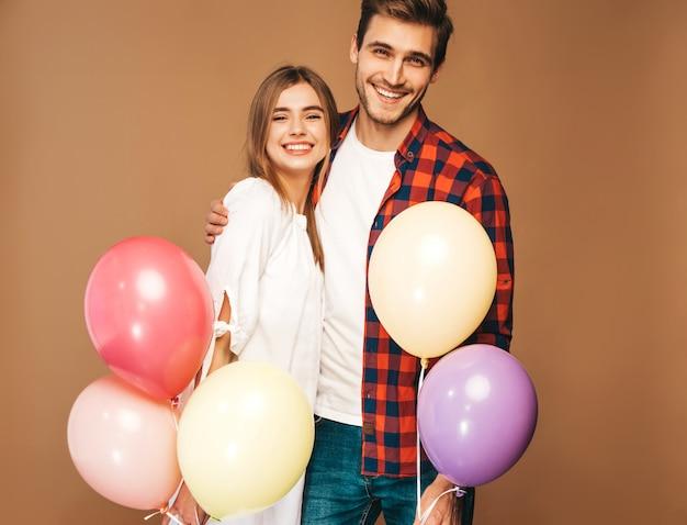 笑顔の美しい少女とカラフルな風船の束を押しながら笑っている彼女のハンサムなボーイフレンドの肖像画。愛の幸せなカップル。お誕生日おめでとうございます 無料写真