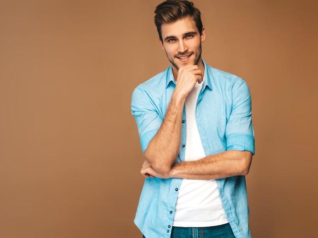 Портрет красивый улыбающийся стильный молодой человек модель, одетая в синюю рубашку одежды. модный мужчина позирует Бесплатные Фотографии