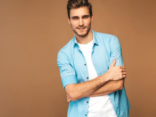 Портрет красивый улыбающийся стильный молодой человек модель, одетая в синюю рубашку одежды. модный мужчина позирует. скрещенные руки Бесплатные Фотографии