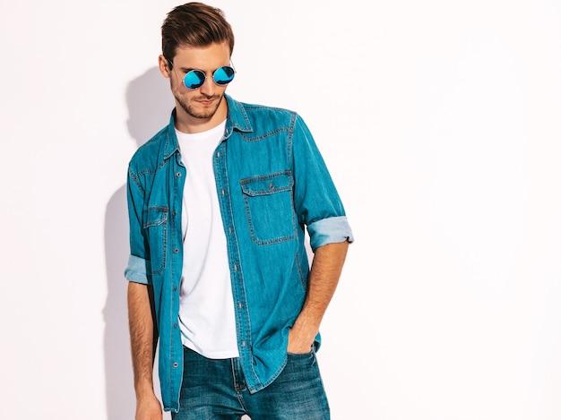 Портрет красивые улыбающиеся стильный молодой человек модель носить джинсовую одежду и очки. модный мужчина Бесплатные Фотографии