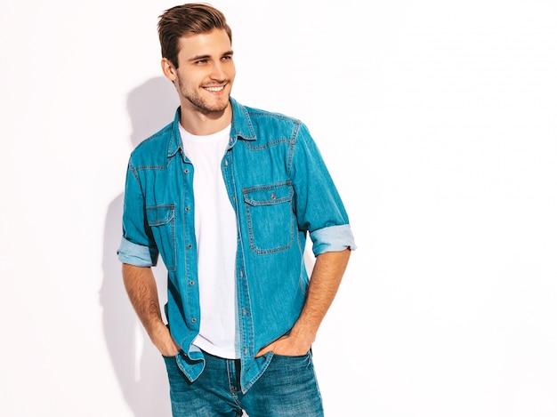 Портрет красивой улыбающейся стильной модели молодого человека оделась в джинсовой одежде. модный мужчина Бесплатные Фотографии