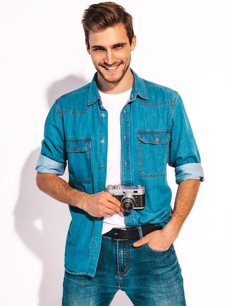 夏のジーンズの服を着てハンサムな笑みを浮かべて男の肖像画。古いビンテージ写真カメラでモデルの男性撮影。 無料写真