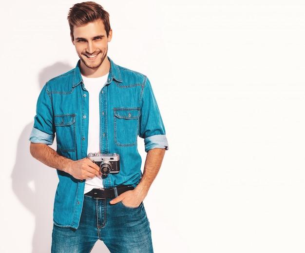 Портрет красавец улыбающегося носить летние джинсы одежды. модельный мужчина фотографируя на старой винтажной камере фото. Бесплатные Фотографии