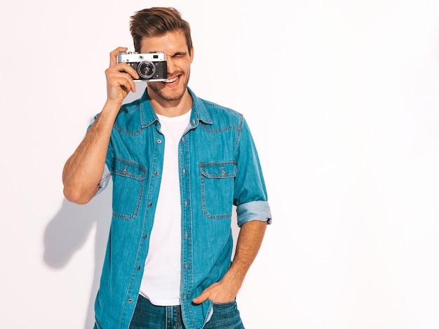 Портрет красавец улыбающегося носить летние джинсы одежды. модельный мужчина держа винтажную камеру фото. Бесплатные Фотографии