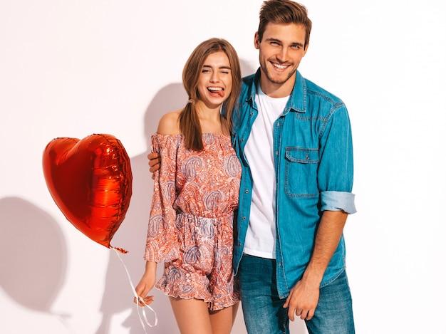 Портрет улыбается красивая девушка и ее красивый парень, держа воздушные шары в форме сердца и смех. счастливая пара в любви. счастливого дня святого валентина. Бесплатные Фотографии