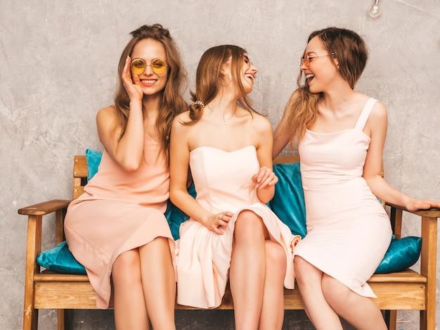 Три молодые красивые улыбающиеся девушки в модных летних розовых платьях. сексуальные беззаботные женщины, сидя на диване в роскошный интерьер. позитивные модели в круглых очках веселятся и общаются Бесплатные Фотографии