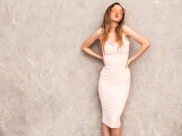 Портрет молодой красивой улыбающейся девушки в модном летнем светло-розовом платье. сексуальная беззаботная женщина позирует. позитивная модель с удовольствием и поцелуем Бесплатные Фотографии