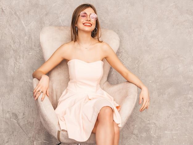 トレンディな夏の淡いピンクのドレスで美しい笑顔少女の肖像画。ベージュの椅子に座っているセクシーな屈託のない女性。豪華なインテリアでポーズ 無料写真