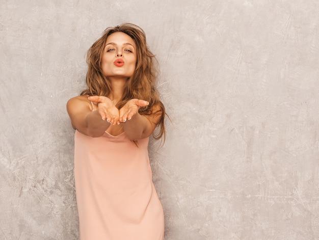Портрет молодой красивой улыбающейся девушки в модном летнем светло-розовом платье. сексуальная беззаботная женщина позирует. позитивная модель с удовольствием. дарим воздушный поцелуй Бесплатные Фотографии