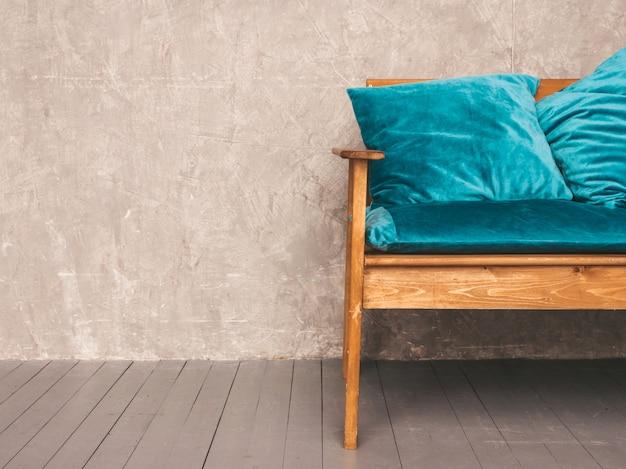 スタイリッシュな布張りの青と木製のモダンなソファと灰色の壁のインテリア 無料写真
