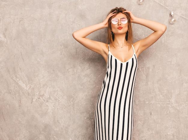 トレンディな夏のシマウマのドレスで美しい笑顔少女の肖像画。セクシーな屈託のない女性がポーズします。ラウンドサングラスで楽しんでいるポジティブなモデル。キスをする 無料写真