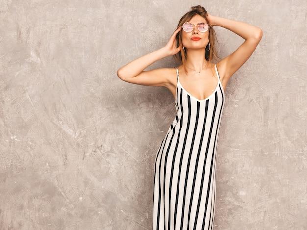 トレンディな夏のシマウマのドレスで美しい笑顔少女の肖像画。セクシーな屈託のない女性がポーズします。ラウンドサングラスで楽しんでいる肯定的なモデル 無料写真