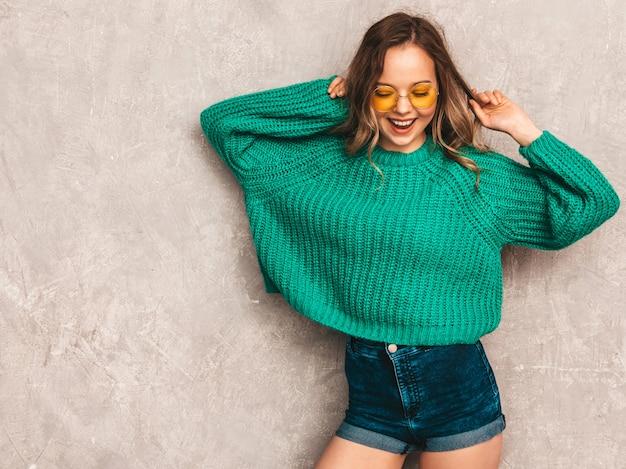 Красивая сексуальная улыбающаяся великолепная девушка в зеленом модном свитере. женщина позирует в круглых очках. модель с удовольствием Бесплатные Фотографии