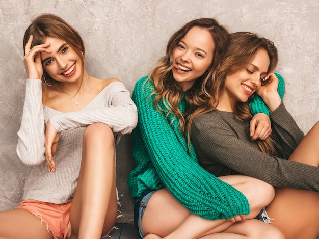 Три молодые красивые улыбающиеся великолепные девушки в модной летней одежде. сексуальные беззаботные женщины позируют. позитивные модели с удовольствием. сидя на полу Бесплатные Фотографии