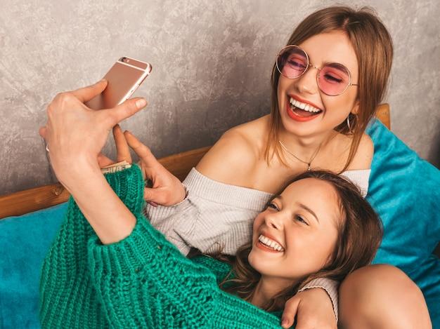 Две молодые красивые улыбающиеся великолепные девушки в модной летней одежде. сексуальные беззаботные женщины, позирующие в интерьере и делающие селфи. позитивные модели с удовольствием со смартфона. Бесплатные Фотографии