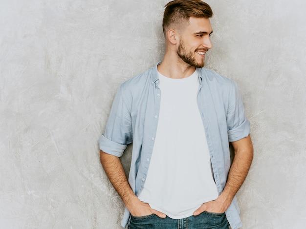 Портрет красивый улыбающийся молодой человек модель носить повседневную рубашку одежду. мода стильный мужчина позирует Бесплатные Фотографии