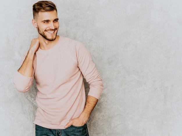 カジュアルな夏のピンクの服を着てハンサムな笑みを浮かべて若い男モデルの肖像画。ファッションスタイリッシュな男のポーズ 無料写真
