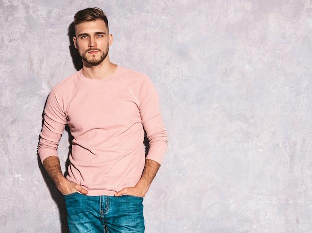 Портрет красивый улыбающийся молодой человек модели носить повседневные летние розовые одежды. мода стильный мужчина позирует Бесплатные Фотографии