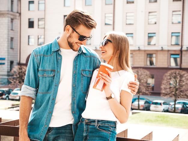 笑顔の美しい少女とカジュアルな夏服で彼女のハンサムなボーイフレンドの肖像画。 。水とストローのボトルを持つ女性 無料写真