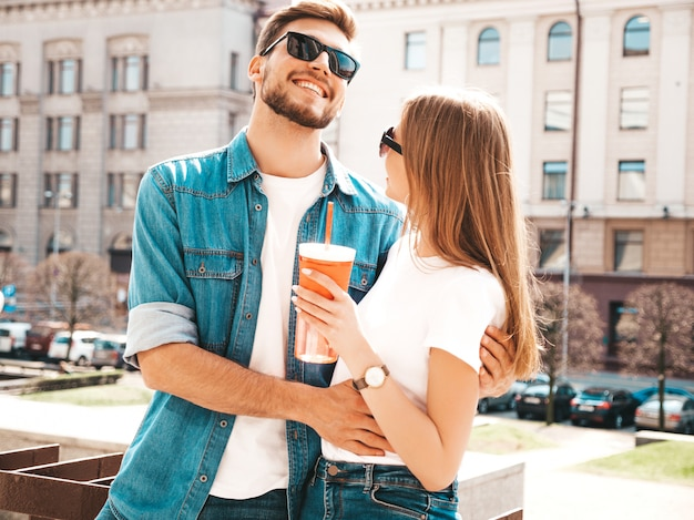 Улыбка красивая девушка и ее красивый парень в повседневной летней одежде. , женщина с бутылкой воды Бесплатные Фотографии