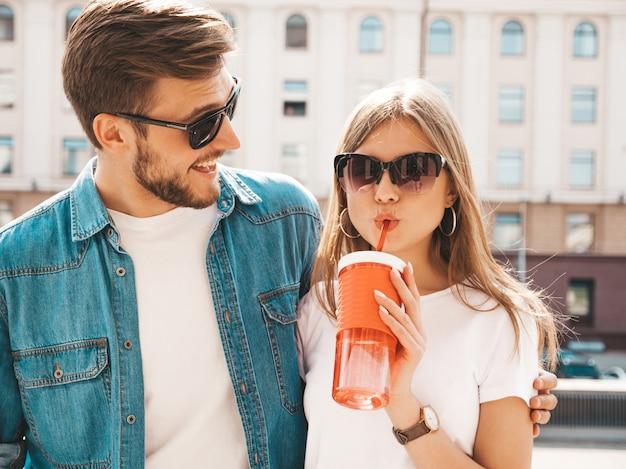 カジュアルな夏服で笑顔の美しい少女と彼女のハンサムなボーイフレンド。 。 。ストローでボトルから女性の飲料水 無料写真