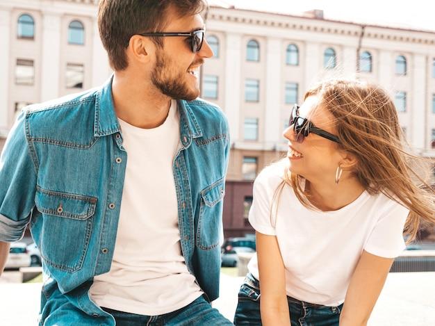 Портрет улыбается красивая девушка и ее красивый парень в непринужденной летней одежды и солнцезащитные очки. , в обнимку Бесплатные Фотографии